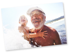 grandpa holding grandchild in waves of water having fun
